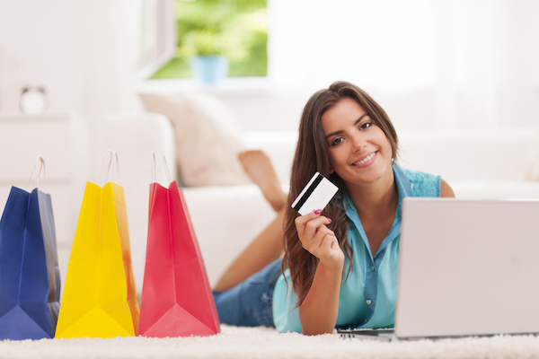 Beautiful woman paying by credit card for shopping at home